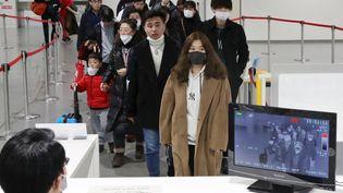 Des passagersen provenance de Wuhan portant des masques à leur arrivée à l'aéroport d'Osaka, au Japon, le 21 janvier 2020. (KEN SATOMI / YOMIURI)