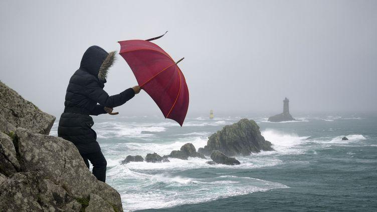 Une femme lutte contre le vent lors d'une tempête, à la pointe du Raz (Finistère), le 21 décembre 2015. (GARCIA JULIEN / HEMIS.FR / HEMIS.FR)