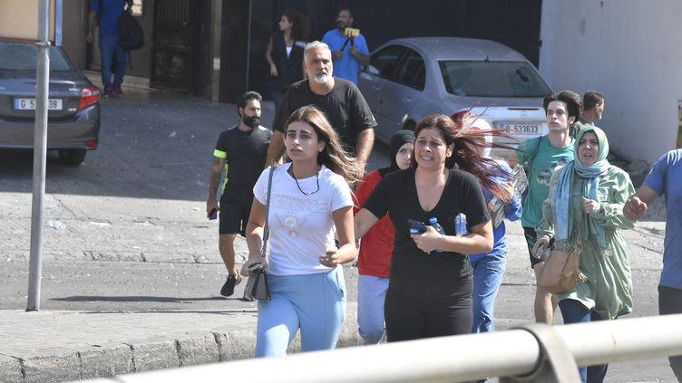 Des habitants de Beyrouth (Liban) fuient les lieux d'une manifestation au cours de laquelle des tirs ont retenti, le 14 octobre 2021. (HUSSAM SHBARO / ANADOLU AGENCY / AFP)