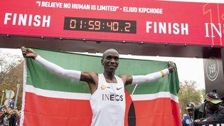 Eliud Kipchoge paradant avec le drapeau du Kenya, après avoir réussi à finir un marathon sous la barre des 2 heures, le 12 octobre 2019. (CHRISTIAN BRUNA / EPA)