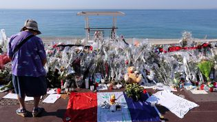 Une femme se tient devant le mémorial pour les victimes de l'attentat sur la promenade des Anglais, le 19 juillet 2016, à Nice (Alpes-Maritimes). (VALERY HACHE / AFP)