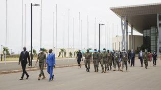 Des chefs militaires maliens accueillent l'ancien président nigérian à l'aéroport de Bamako, avant une réunion entre des chefs militaires maliens et une délégation de la Cédéao, le 22 août 2020. (ANNIE RISEMBERG / AFP)