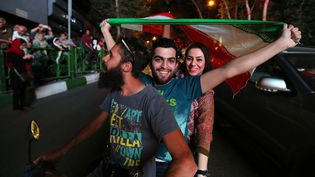 Des Iraniens célèbrent l'accord sur le nucléaire dans les rues de Téhéran, le 14 juillet 2015. (ATTA KENARE / AFP)