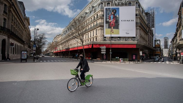 Un homme traverse à vélo une rue vide devant les Galeries Lafayette à Paris, le 18 mars 2020. (MARTIN BUREAU / AFP)