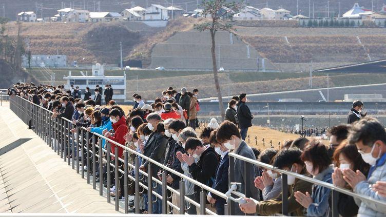 Des Japonais réunis le 11 mars 2021 àRikuzen-Takata, ville côtière du nord-est du Japon, pour rendre hommage au victimes de la triple catastrophe du 11 mars 2011. (TETSU JOKO / YOMIURI / AFP)
