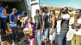 Des migrants reçoivent de la nourriture distribuée par l'association L'auberge des migrants dans un camp de réfugiés, à Calais (Pas-de-Calais), le 8 août 2015. (PHILIPPE HUGUEN / AFP)