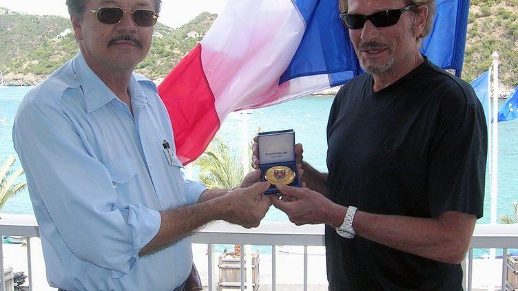 Bruno Magras et Johnny Hallyday, le18 fevrier 2006, l'occasion d'un cocktail sur la terrasse de l'hôtel de ville de Gustavia (Saint Barthélemy). (MAXPPP)