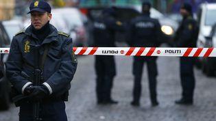 Des policiers se tiennent devant l'entrée d'un cybercafé de Copenhague, où deux personnes ont été arrêtées, le 15 février 2015, au lendemain de deux attentats qui ont coûté la vie à deux hommes. (LEONHARD FOEGER / REUTERS)
