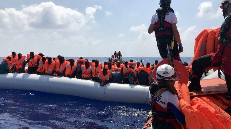 Les membres d'équipage de l'Ocean Viking, le samedi 10 août, alors qu'ils portent secours aux migrants embarqués sur un matelas pneumatique. (ANNE CHAON / AFP)