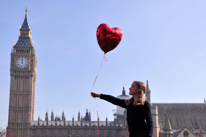 Mili Baxter, 9 ans, lâche un ballon devant le parlement britannique pour soutenir l'opération #Withsyria  (CARL COURT / AFP)