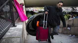 Un migrant évacue le camp de la gare d'Austerlitz à Paris, le 17 septembre 2015. (FLORIAN DAVID / AFP)