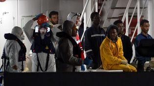 Des rescapés arrivent dans le port de Catane (Italie) le 20 avril 2015, après le naufrage de leur chalutier au large des côtes libyennes. (ALBERTO PIZZOLI / AFP)