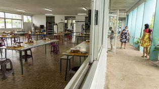 Une écolière arrive à la cantine, le 18 mai 2020, à Papeete (Polynésie française). (SULIANE FAVENNEC / AFP)