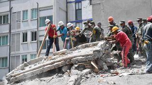 Secouristes et volontaires s'affairent pour retrouver des survivants, le 20 septembre 2017 à Mexico (Mexique). (YURI CORTEZ / AFP)