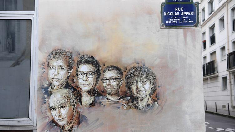 De droite à gauche, les portraits de Bernard Maris, Wolinski, Tignous, Charb et Cabu, décédés lors de l'attaque de Charlie Hebdo, le 7 janvier 2015. (CHRISTOPHE ARCHAMBAULT / AFP)