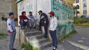 """Un groupe de jeunes Algériens dans un quartier populaire de la capitale Alger en février 2019 au moment du déclenchement du """"Hirak"""", un vaste mouvement de protestation. (RYAD KRAMDI / AFP)"""
