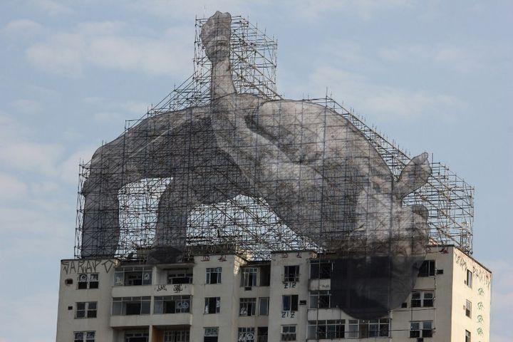 JR : installationperchée sur le toit d'un immeuble de 20 étages dans le quartier de Flamengo, à Rio, saisit le sauteur en hauteur soudanais Mohamed Younes Drisse arque-bouté sur le dos en plein envol, comme sur le point de franchir le sommet du bâtiment.  (Luiz Souza / NurPhoto)
