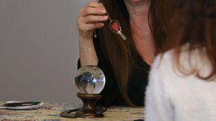Une voyante avec sa boule de cristal et son pendule. (JEAN-FRAN?OIS FREY / MAXPPP)