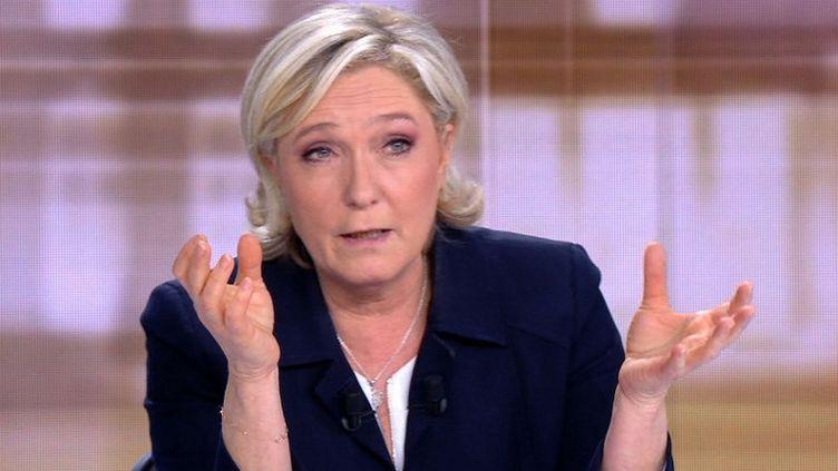 """Emmanuel Macron a accusé mercredi Marine Le Pen d'être """"l'héritière d'un système"""", la candidate FN répliquant en le décrivant comme """"l'héritier de François Hollande"""". (STRINGER / AFP)"""