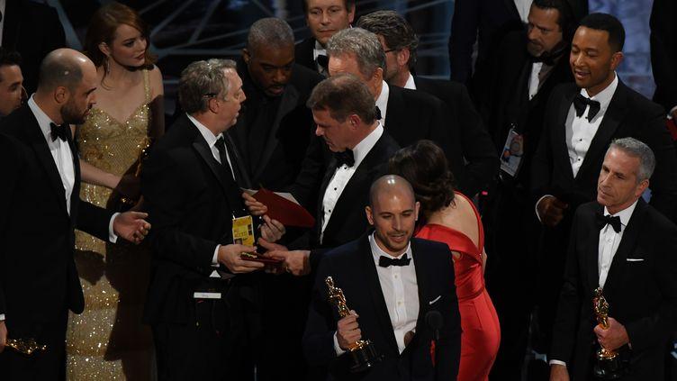 """Un des producteurs de """"La La Land"""" prononce son discours de remerciement après la victoire du film aux Oscars, tandis que, derrière-lui, les organisateurs réalisent qu'elle a été annoncée par erreur, le 26 février 2017 à Los Angeles. (MARK RALSTON / AFP)"""