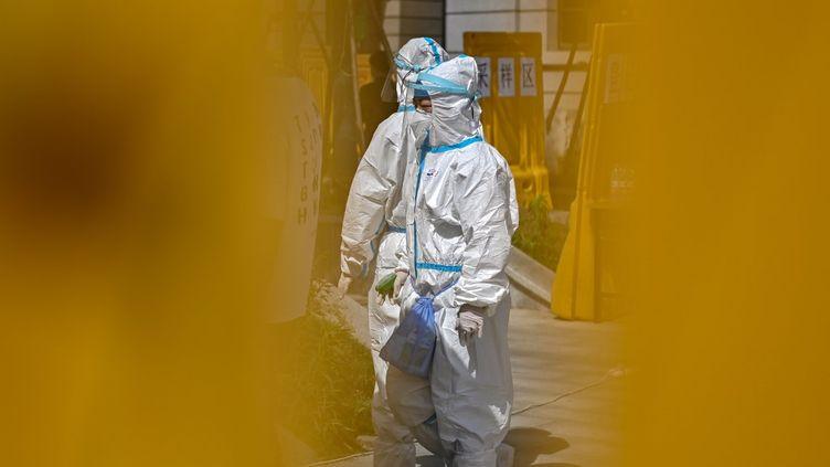 Des membres du personnel soignant se préparent à tester des patients au Covid-19, lundi 18 mai 2020 à Wuhan (Chine). (HECTOR RETAMAL / AFP)