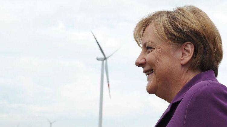 La chancelière allemande Angela Merkel posant devant des éoliennes à Krempin, au nord de l'Allemagne, en août 2010, lors d'une «tournée de l'énergie». (JOHANNES EISELE / AFP)