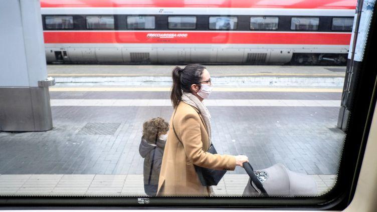 Une passagère portant un masque sur le quai de la gare de Milan, en Italie, le 25 février 2020. (ANDREAS SOLARO / AFP)