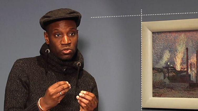 """La rappeur, écrivain et réalisateur Abd Al Malik commente le tableau """"Usines près de Charleroi"""" de Maximilien Luce exposé au Musée d'Orsay. (CAPTURE D'ECRAN YOUTUBE/MUSEE D'ORSAY)"""