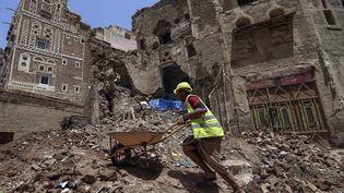 Un ouvrier ramasse les décombres d'un bâtiment classé au patrimoine mondial de l'Unesco qui s'est effondré suite à de fortes pluies, dans le quartier de la vieille ville à Sanaa, au Yémen, le 12 août 2020. (MOHAMMED HUWAIS / AFP)