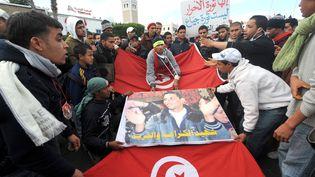 Des habitants de Kasserine portent une affiche de Mohamed Bouazizi, devant le palais du gouvernement à Tunis, le 28janvier 2011. (FETHI BELAID / AFP)