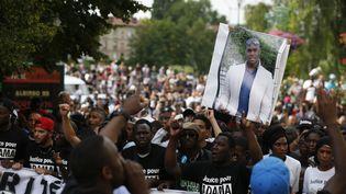 Des manifestants portent un portrait d'Adama Traoré, le 22 juillet 2016 àBeaumont-sur-Oise (Val-d'Oise). (THOMAS SAMSON / AFP)