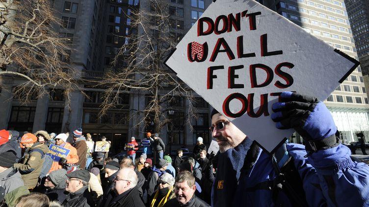 Un employé gouvernemental opposé à la construction d'un mur entre les Etats-Unis et le Mexique manifeste son hostilité au projet dans les rues de Boston, vendredi 11 janvier 2019. (JOSEPH PREZIOSO / AFP)