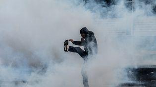 Un manifestant lance une grenade lacrymogène lors d'une manifestation à Diyarbakir (Turquie) le 22 décembre 2015 (ILYAS AKENGIN / AFP)