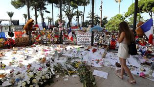 Une femme se recueille devant le mémorial aux victimes de l'attentat à Nice (Alpes-Maritimes), le 19 juillet 2016. (VALERY HACHE / AFP)