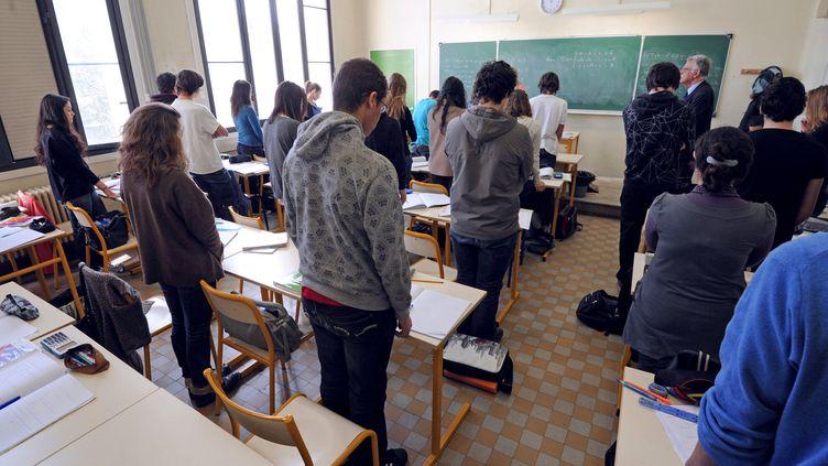 Des élèves et leur professeur observent une minute de silence à Marseille (Bouches-du-Rhône), le 20 mars 2012, à la mémoire des victimes de la tuerie à l'école de Toulouse. (ANNE-CHRISTINE POUJOULAT / AFP)