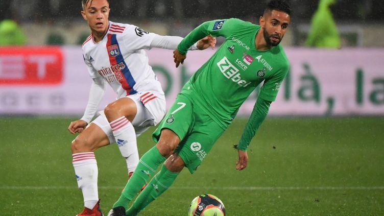 Ryad Boudebouz et Maxence Caqueret lors du match ASSE-Lyon, le 3 octobre 2021, à Geoffroy-Guichard. (PHILIPPE DESMAZES / AFP)