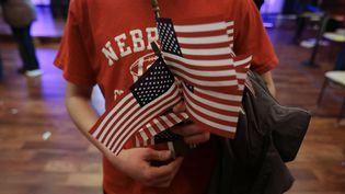 Un homme tient des drapeaux américains au meeting de Ben Carson, candidat aux primaires républicaines, à Des Moines (Etats-Unis), le 30 janvier 2016. (CHRIS CARLSON / AP / SIPA)