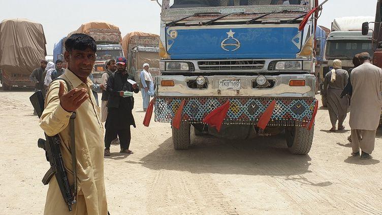Des agents de sécurité en civil montent la garde alors que des camions de marchandises se préparent à se diriger vers le poste frontière afghan de Chaman, après la réouverture partielle d'un point de passage clé entre le Pakistan et l'Afghanistan, quelques jours après que les talibans ont pris le contrôle de la ville frontalière afghane dans le cadre d'une offensive rapide à travers le pays. (ASGHAR ACHAKZAI / AFP)