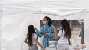 Des jeunes filles se font tester au Covid-19 dans une tente dans une rue de Paris, le 25 février 2021. (MAGALI COHEN / HANS LUCAS / AFP)