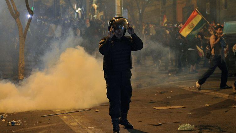 Un policier face à des manifestants, à La Paz (Bolivie), le 22 octobre 2019. (JORGE BERNAL / AFP)