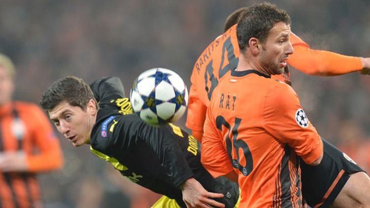 Razvan Rat (Donetsk) à la lutte avec Robert Lewandowski (Dortmund) (SERGEI SUPINSKY / AFP)