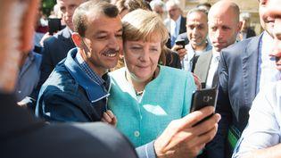 Angela Merkel avec les réfugiés devant un centre d'accueil pour demandeurs d'asile, à Berlin, le 10 septembre à 2015. (BERND VON JUTRCZENKA / DPA / REUTERS)