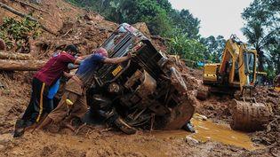 Des secouristes poussent un véhicule renversé coincé dans la boue et les débris sur le site d'un glissement de terrain causé par de fortes pluies à Kokkayar, dans l'État indien du Kerala, le 17 octobre 2021. (AFP)
