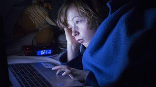 Un adolescent, dans son lit, regarde un écran, le 15 mars 2021, à Toulouse (Haute-Garonne). (ARNAUD CHOCHON / HANS LUCAS / AFP)