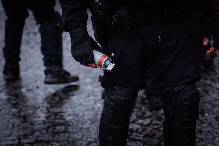 """Un officier de police tient une grenade explosive GLI-F4 dans la main lors d'une manifestation de """"gilets jaunes"""" à Paris, le 26 janvier 2019, sur la place de la Bastille. (KARINE PIERRE / HANS LUCAS)"""