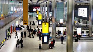 Des passagers récupèrent leurs bagages dans le terminal 5 de l'aéroport d'Heathrow, à Londres (Royaume-Uni), le 19 décembre 2018. (AFP)