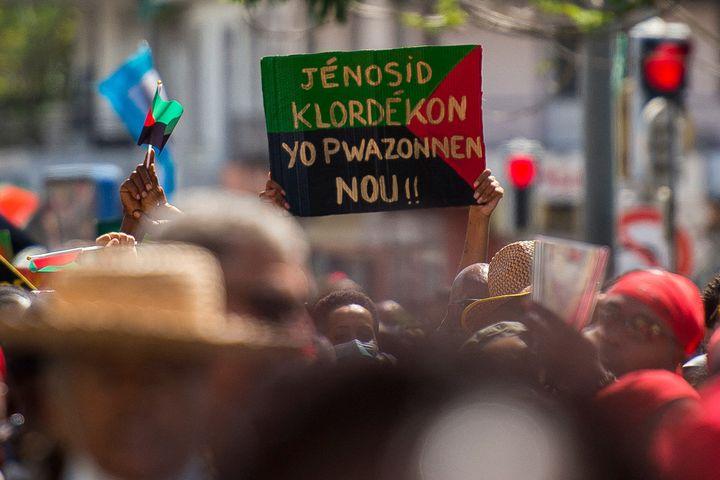 """Un panneau dénonce : """"génocide au chlordécone, ils nous ont empoisonnés"""", lors d'une manifestation à Fort-de-France (Martinique), le 27 février 2021. (LIONEL CHAMOISEAU / AFP)"""