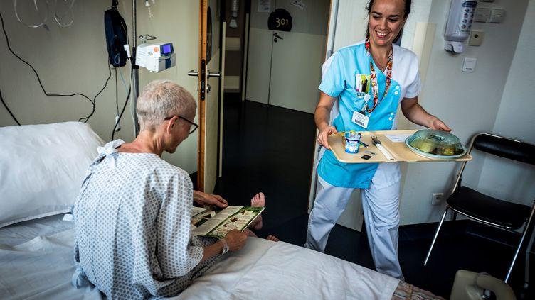 Un patient se fait servir un repas à l'hôpital, le 10 septembre 2018, à l'hôpitalLéon-Berard, à Lyon. (JEAN-PHILIPPE KSIAZEK / AFP)