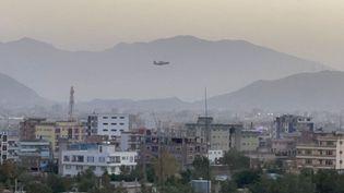 Un avion dans le ciel de Kaboul (Afghanistan), le 26 août 2021, après une double explosion près de l'aéroport. (HAROON SABAWOON / ANADOLU AGENCY / AFP)