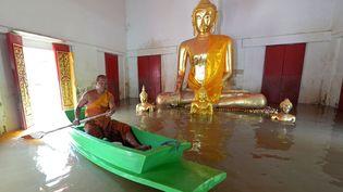 Un moine bouddhiste se déplace en barque dans un temple inondé d'Ayutthaya (Thaïlande), le 3 octobre 2013. (PORNCHAI KITTIWONGSAKUL / AFP)